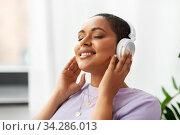 Купить «woman in headphones listening to music at home», фото № 34286013, снято 24 мая 2020 г. (c) Syda Productions / Фотобанк Лори
