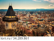 Graz, Austria - 10.03.2020: Uhrturm landmark in Graz cityscape view, Styria region of Austria. Clocktower against cityscape. Стоковое фото, фотограф Zoonar.com/Przemyslaw Iciak / easy Fotostock / Фотобанк Лори