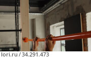 Купить «man exercising on bar and doing pull-ups in gym», видеоролик № 34291473, снято 11 июля 2020 г. (c) Syda Productions / Фотобанк Лори