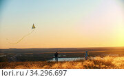 Young family playing with kite on the wheat field on sunset - father holding the rope of kite. Стоковое видео, видеограф Константин Шишкин / Фотобанк Лори