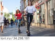Trendy fashinable teenager girls riding public rental electric scooters in urban city environment. New eco-friendly modern public city transport in Ljubljana, Slovenia. Стоковое фото, фотограф Matej Kastelic / Фотобанк Лори