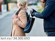 Mann als Dieb beim Stehlen aus der Tasche einer unaufmerksamen Frau. Стоковое фото, фотограф Zoonar.com/Robert Kneschke / age Fotostock / Фотобанк Лори