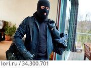 Vermummter Einbrecher flüchtet aus Haus mit Tasche voller Beute. Стоковое фото, фотограф Zoonar.com/Robert Kneschke / age Fotostock / Фотобанк Лори