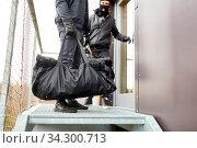 Zwei Einbrecher flüchten mit Tasche voller Beute aus Büro. Стоковое фото, фотограф Zoonar.com/Robert Kneschke / age Fotostock / Фотобанк Лори