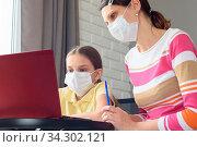 Girl and tutor in medical masks study remotely online. Стоковое фото, фотограф Zoonar.com/Ivanov Aleksey y / easy Fotostock / Фотобанк Лори