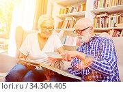 Paar Senioren schaut gemeinsam Foto im Fotoalbum zur Erinnerung an im Seniorenheim. Стоковое фото, фотограф Zoonar.com/Robert Kneschke / age Fotostock / Фотобанк Лори