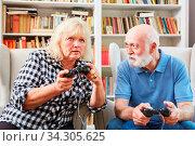 Senioren Paar als vitale Rentner beim Videospiel mit Konsole im Wohnzimmer. Стоковое фото, фотограф Zoonar.com/Robert Kneschke / age Fotostock / Фотобанк Лори