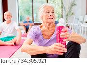 Senior Frau in einer Pause im Yogakurs mit einer Flasche Wasser als Erfrischung. Стоковое фото, фотограф Zoonar.com/Robert Kneschke / age Fotostock / Фотобанк Лори