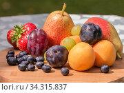 Купить «На деревянной доске лежат свежие натуральные фрукты и ягоды», фото № 34315837, снято 25 июля 2020 г. (c) Людмила Капусткина / Фотобанк Лори