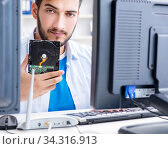 Купить «Technician with broken hard drive», фото № 34316913, снято 6 июля 2017 г. (c) Elnur / Фотобанк Лори