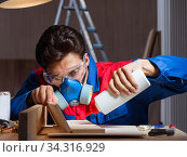 Young man gluing wood pieces together in DIY concept. Стоковое фото, фотограф Elnur / Фотобанк Лори