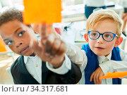 Kinder als Business Leute im Brainstorming Workshop notieren Ideen auf Zettel. Стоковое фото, фотограф Zoonar.com/Robert Kneschke / age Fotostock / Фотобанк Лори