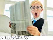 Junge mit offenem Mund als staunender Geschäftsmann beim Lesen einer Zeitung. Стоковое фото, фотограф Zoonar.com/Robert Kneschke / age Fotostock / Фотобанк Лори