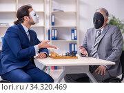 Two businessmen playing chess wearing masks. Стоковое фото, фотограф Elnur / Фотобанк Лори