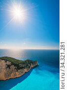 Vertical view of the sun shining over cliffs in Shipwreck Cove in summer on Zante Island, Greece. Стоковое фото, фотограф Zoonar.com/Pawel Opaska / easy Fotostock / Фотобанк Лори