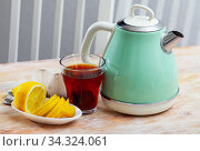 Modern electric kettle, cup and lemon on table in kitchen. Стоковое фото, фотограф Яков Филимонов / Фотобанк Лори
