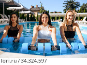 Smiling woman with dumbbells in pool outdoors. Стоковое фото, фотограф Tryapitsyn Sergiy / Фотобанк Лори