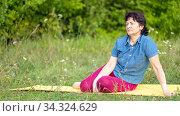 Beautiful mature women sits in Zelenaya Polyana on the mat after gymnastics on a summer day. Стоковое фото, фотограф Акиньшин Владимир / Фотобанк Лори