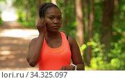 Купить «african woman with earphones and smart watch», видеоролик № 34325097, снято 10 июля 2020 г. (c) Syda Productions / Фотобанк Лори