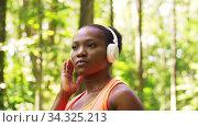 Купить «african woman with headphones and smart watch», видеоролик № 34325213, снято 10 июля 2020 г. (c) Syda Productions / Фотобанк Лори