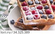 Купить «Belgian waffles on plate with berries», видеоролик № 34325389, снято 8 июля 2020 г. (c) Сергей Петерман / Фотобанк Лори