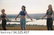 Three young women doing aerobic exercises outdoors - jumping on one spot. Стоковое видео, видеограф Константин Шишкин / Фотобанк Лори