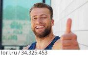 Купить «portrait of smiling young man showing thumbs up», видеоролик № 34325453, снято 5 июля 2020 г. (c) Syda Productions / Фотобанк Лори
