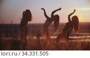 Three young women doing aerobic movements on sunset. Стоковое видео, видеограф Константин Шишкин / Фотобанк Лори