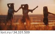 Three young women doing aerobic dance and slow movements with their hands on sunset. Стоковое видео, видеограф Константин Шишкин / Фотобанк Лори