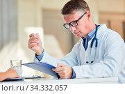 Arzt als Klinik Chef in der Verwaltung liest eine Akte und macht die Terminplanung. Стоковое фото, фотограф Zoonar.com/Robert Kneschke / age Fotostock / Фотобанк Лори
