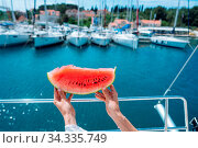 Slice of ripe watermelon in female hands against the background of yachts. Стоковое фото, фотограф Zoonar.com/Oleksii Hrecheniuk / easy Fotostock / Фотобанк Лори