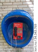Красный таксофон висит на кирпичной стене. Редакционное фото, фотограф Мария / Фотобанк Лори