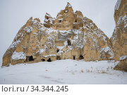 Solitary rock with ancient dwellings on a cloudy January day. Cappadocia (2015 год). Стоковое фото, фотограф Виктор Карасев / Фотобанк Лори