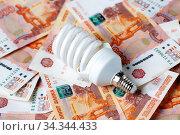 Экономия электроэнергии. Энергосберегающая лампа и деньги. Стоковое фото, фотограф Иван Карпов / Фотобанк Лори