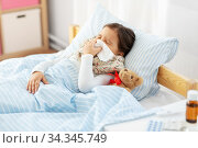 sick girl lying in bed and blowing nose at home. Стоковое фото, фотограф Syda Productions / Фотобанк Лори