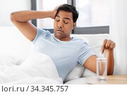 sick man in bed with medicine and glass of water. Стоковое фото, фотограф Syda Productions / Фотобанк Лори