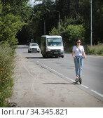 Купить «Балашиха, девушка на электрическом самокате движется по обочине дороги», эксклюзивное фото № 34345821, снято 3 августа 2020 г. (c) Дмитрий Неумоин / Фотобанк Лори