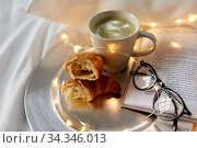 Купить «croissants, matcha tea, book and glasses in bed», фото № 34346013, снято 22 января 2020 г. (c) Syda Productions / Фотобанк Лори