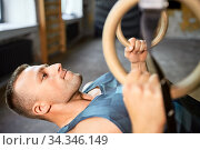 man doing exercising on gymnastic rings in gym. Стоковое фото, фотограф Syda Productions / Фотобанк Лори