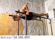 man doing push-ups on parallel bars in gym. Стоковое фото, фотограф Syda Productions / Фотобанк Лори