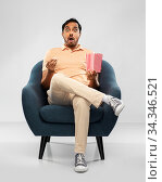 shocked indian man eating popcorn in chair. Стоковое фото, фотограф Syda Productions / Фотобанк Лори