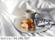 Купить «croissants, cup of coffee and book in bed at home», фото № 34346581, снято 22 января 2020 г. (c) Syda Productions / Фотобанк Лори