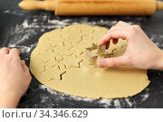 hands cutting dough with star mold on table. Стоковое фото, фотограф Syda Productions / Фотобанк Лори