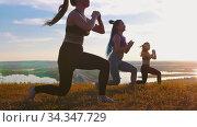 Fitness on nature - three young women doing aerobic exercises on sunset - doing lunges. Стоковое видео, видеограф Константин Шишкин / Фотобанк Лори