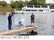 Maedchen in einem Wasser Laufball, im Hintergrund das Motorschiff... Стоковое фото, фотограф Zoonar.com/Stefan Ziese / age Fotostock / Фотобанк Лори