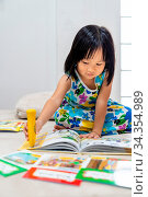 Asian girl child reading interactive book in living room at home as... Стоковое фото, фотограф Zoonar.com/Vichie81 / easy Fotostock / Фотобанк Лори