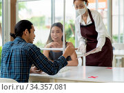 Asian waitress wear face mask and face shield using tablet to show... Стоковое фото, фотограф Zoonar.com/Vichie81 / easy Fotostock / Фотобанк Лори
