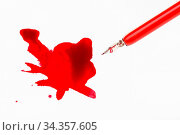 Top view of red nib pen over red ink stain on white paper. Стоковое фото, фотограф Zoonar.com/Valery Voennyy / easy Fotostock / Фотобанк Лори