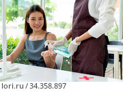 Waitress push alcohol gel hand sanitizer for customer at dining table... Стоковое фото, фотограф Zoonar.com/Vichie81 / easy Fotostock / Фотобанк Лори