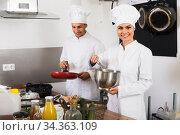 Купить «Two cheerful female and male cooks», фото № 34363109, снято 4 августа 2020 г. (c) Яков Филимонов / Фотобанк Лори